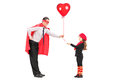 Male superhero giving a balloon to a little girl isolated on white background Stock Photo