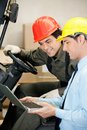 Male supervisor and forklift driver using laptop young at warehouse Stock Photography