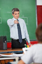 Male teacher pointing at schoolboy mature in classroom Royalty Free Stock Image