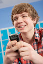 Male Teenage Student Using Mobile Phone Stock Photo