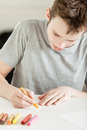 Male teenager making art on paper using crayons close up white at the table Stock Photos