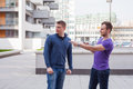 Male tourist asks for directions from man with mobile phone at c Royalty Free Stock Photo