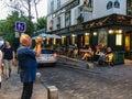 Male tourist shoots video outside La Bonne Franquette, noted cabaret on Montmartre in Paris, France Royalty Free Stock Photo