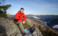 Male tourist sitting on rock on top of the mountain Royalty Free Stock Photo