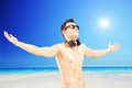 Male tourist with speakerphones spreading his arms next to a se and gesturing freedom sea on sunny day Royalty Free Stock Image