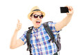 Male tourist taking pictures of himselves with phone and giving backpack mobile thumb up isolated on white background Royalty Free Stock Photography