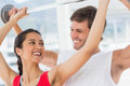 Male trainer helping fit woman to lift the barbell happy young women in gym Stock Images