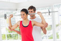 Male trainer helping fit woman to lift the barbell happy young women in gym Stock Image