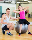 Male trainer with woman doing crunches on the ball Royalty Free Stock Photo