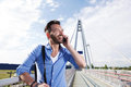 Male traveler standing on bridge and talking on cell phone Royalty Free Stock Photo