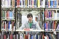 Male university student amid books in library portrait of a young Stock Photo