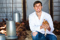 Male vet holding chicken in hen house Royalty Free Stock Photo