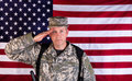 Male veteran solider saluting with USA flag in background while Royalty Free Stock Photo