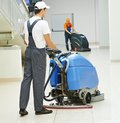 Male worker cleaning business hall cleaner man workers with mop in uniform corridor pass or floor of building Royalty Free Stock Photo