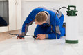 Male worker spraying pesticide on cabinet kneeling floor and wooden Royalty Free Stock Photos