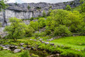 Malham cove yorkshire dales national park sweep of the limestone cliff of england uk with the stream running in front of it Stock Images