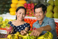 In the mall close up image of a senior couple buying fruits and vegetables market on foreground Stock Image