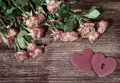 Mall pink garden roses and hearts on wooden surface. Retro style romantic floral background. Valentines day background. Royalty Free Stock Photo