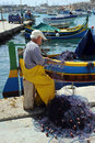 Maltese fisherman working his nets against backdrop traditional maltese luzzu fishing boats marsaxlokk harbor mediterranean island Stock Photos