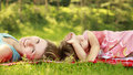 Mama and her little daughter lie on the grass a Stock Images