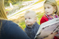 Mamma reading a book to her two adorable blonde children mother wearing winter coats outdoors Royalty Free Stock Images
