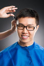 Man�s cutting vertical portrait of a young man having haircut over a grey background Stock Image