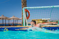 Man in action trying to catch the ball in pool playing water pol Royalty Free Stock Photo