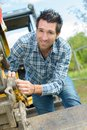 Man adjusting linkage on digger bucket Royalty Free Stock Photo