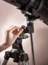 Man adjusts a telescope closeup
