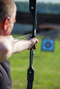 Man aiming bow at target outdoors Stock Photography