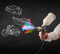 Man with airbrush spray paint with car boat and motorcycle draw drawing on dark background Stock Image