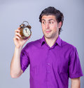 Man with alarm clock handsome on gray background Royalty Free Stock Photography