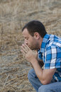 Man alone in prayer in a field. Royalty Free Stock Photo