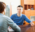 A man answering questions guy talking with employee with laptop in home Royalty Free Stock Images