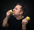 Man with an appetite eating a green apple middle aged in black Royalty Free Stock Image