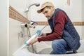 Man applying silicone sealant in the bathroom.
