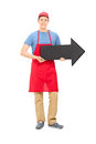 Man in apron holding a big black arrow full length portrait of pointing right isolated on white background Stock Photo