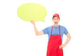 Man in apron holding a blank yellow speech bubble isolated on white background Stock Images