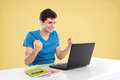 Man with arms raised using laptop portrait of happy young student while Stock Image