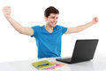 Man with arms raised using laptop portrait of young student Stock Photo