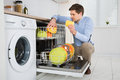 Man arranging dishes in dishwasher young happy modern kitchen Royalty Free Stock Photo