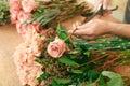 Man assistant in flower shop delivery make rose bouquet closeup