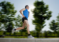 Man with athletic legs running in city park with trees on the background on summer training session fitness healthy lifestyle conc Royalty Free Stock Photo