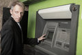 Man at an atm maching glancing over his shoulder Royalty Free Stock Photo