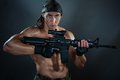 Man with an automatic weapon military he is holding he has big muscles Stock Photography