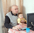 Man with baby working computer at home Royalty Free Stock Photos