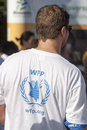 Man in the back wearing white wfp t shirt a he is a of world food programme and a bandana on his right arm sunny and bright Royalty Free Stock Photo