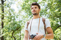 Man with backpack and old photo camera standing in forest Royalty Free Stock Photo