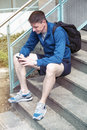 Man with backpack sitting outdoors on stairs with phone Royalty Free Stock Photo
