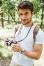 Man with backpack taking photos using old camera in forest Royalty Free Stock Photo